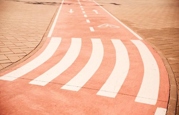 Attraversare a piedi e segno di freccia direzionale sulla pista ciclabile con marciapiede