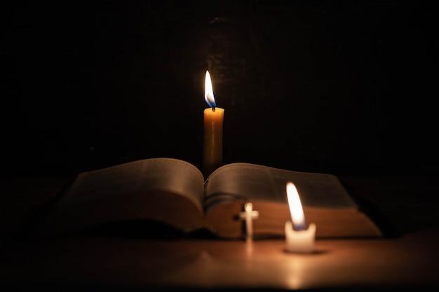오래 된 오크 나무 테이블에 성경과 촛불으로 교차. 무료 사진