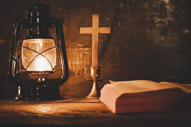Cross with bible and candle on a old oak wooden table