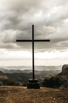Cross with an overlooking view of mountains under a cloudy gray sky