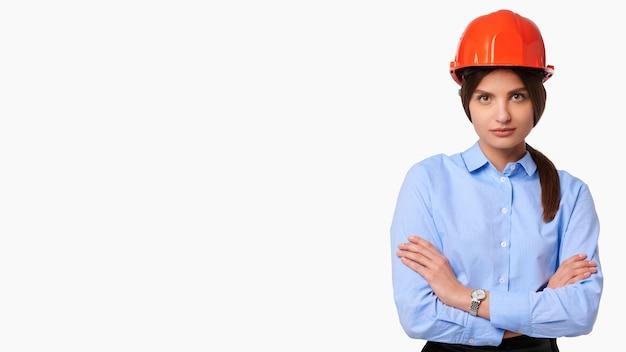 白の隔離されたヘルメットの交差腕白人女性エンジニア
