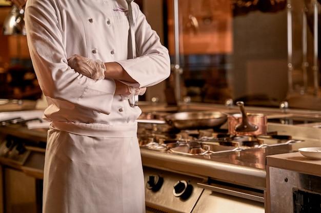 炊飯器の横にあるレストランのシェフの腕を組んで