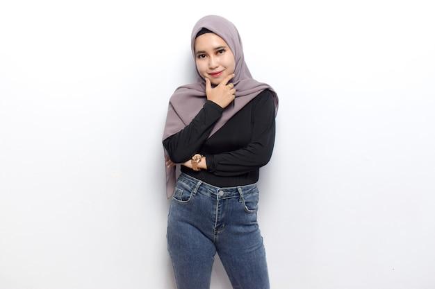 팔짱을 끼고 미소 짓고 젊은 아름다운 이슬람 아시아 여성의 카메라를 보고 베일 히잡을 입는다
