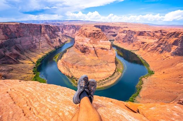 Скрещенные ноги отдыхают, наблюдая за хорсшу-бенд и рекой колорадо на заднем плане, аризона. соединенные штаты