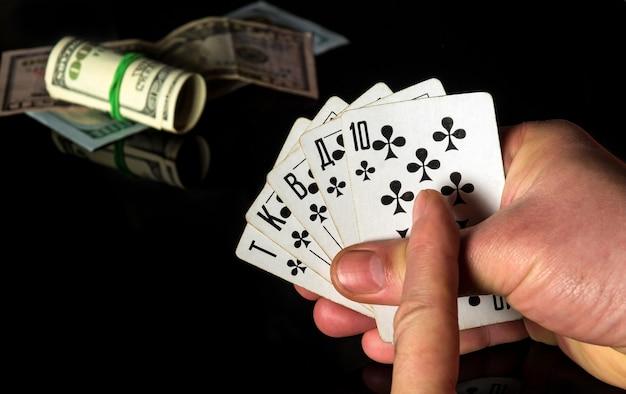 交差した指は幸運をもたらします。ロイヤルフラッシュの組み合わせのポーカーカード。