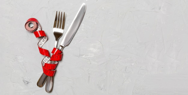 交差したフォークとナイフは灰色のメジャーテープで包まれています。