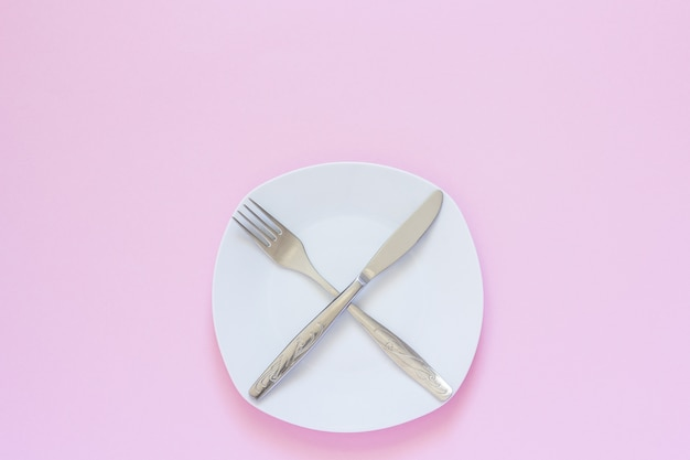 Crossed fork and knife on white plate on pink background.