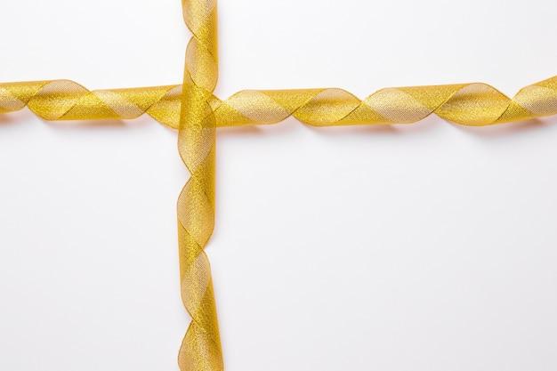 Crossed golden ribbons on white background