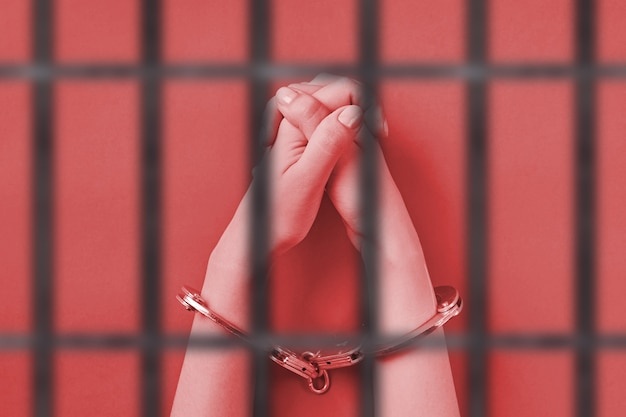 Crossed hands in handcuffs, behind bars. life imprisonment concept. deprivation of liberty and catch perpetrators.