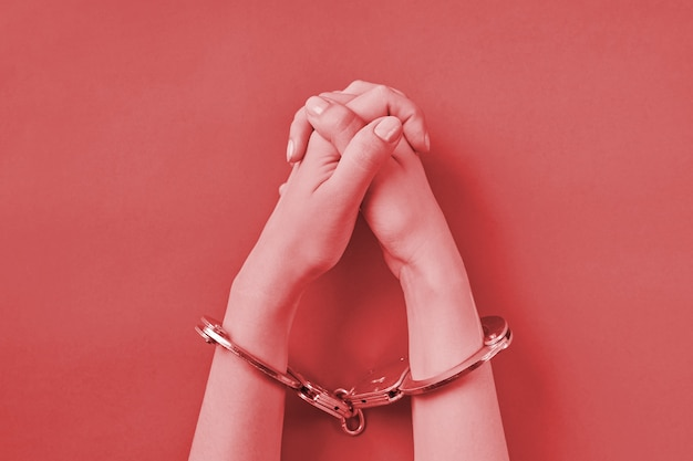 Crossed hands in handcuffs on red background. life imprisonment concept. deprivation of liberty and catch perpetrators.