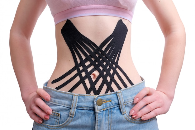 Crossed kinesio tape on the belly of young girl
