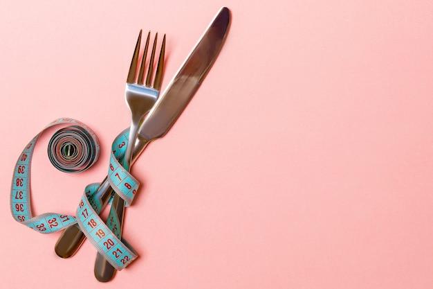 測定テープで接続された交差したナイフとフォーク