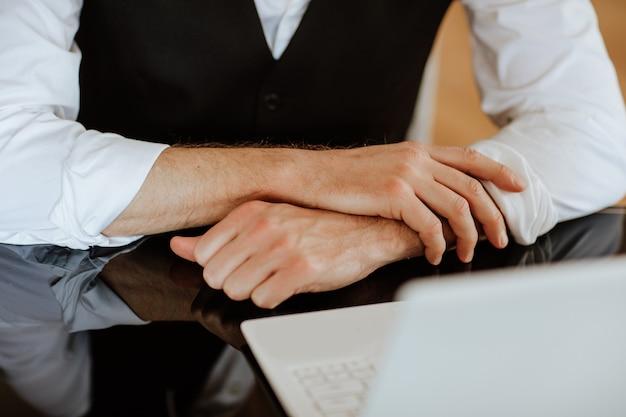 暗いガラスのテーブルに置かれた白いラップトップの近くで男の手を交差させた。焦点は手元にあります。ビジネスコンセプト。