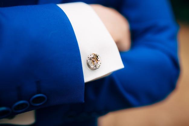 파란색 재킷 커프스 링크로 그의 가슴에 남자의 손을 교차