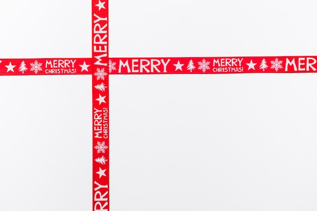 Crossed red ribbons saying merry christmas