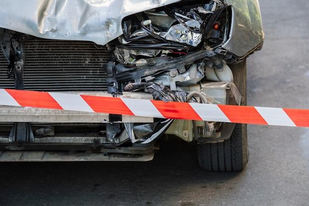交通事故の前で赤白の警告テープを交差させた。赤い警告テープで囲われた道路上の車のボンネットが壊れています。壊れたバンパーとライト付きの車のヘッドライト誰もいない路面アスファルト。