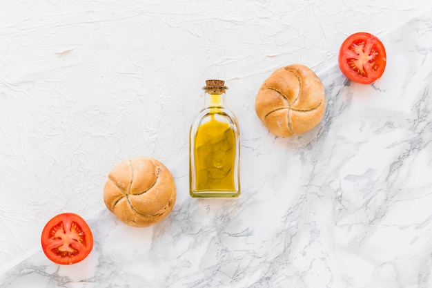Crossed row of bun, tomato and oil bottle on two different backdrop