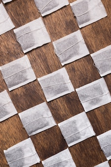 Crossed white tea bag on wooden textured backdrop