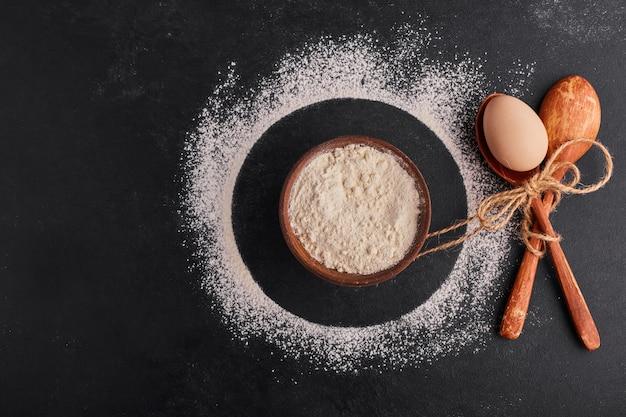 Скрещенные деревянные ложки с яйцом внутри и чашкой муки вокруг.