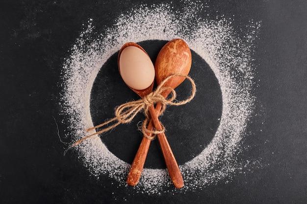 Скрещенные деревянные ложки с яйцом внутри.