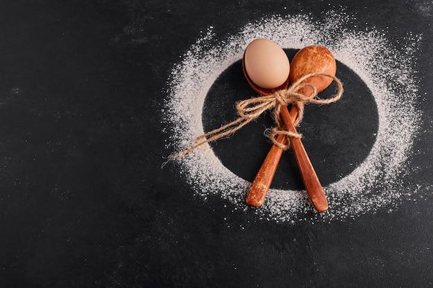 Cucchiai di legno incrociati con dentro un uovo su superficie nera.