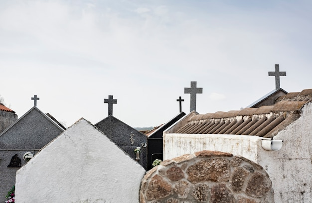 Crosses on the roofs of the pantheons in a cemetery religious concept