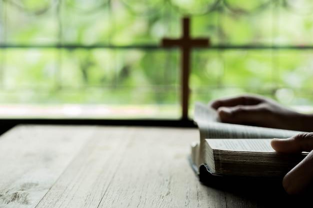 木製のテーブルで聖書の上に開く十字架