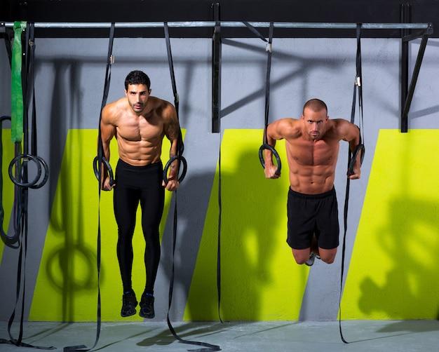 Crossfitディップリングジムで2人の男性のエクササイズ