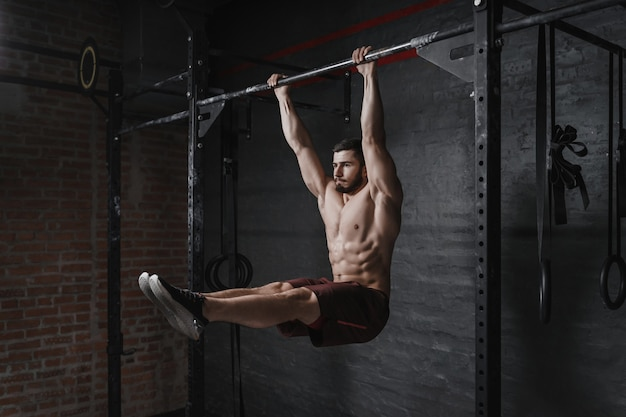 Crossfit athlete doing abs exercise on horizontal bar at the gym