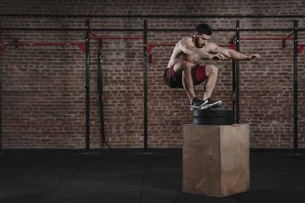 ジムでボックスジャンプ運動をしているcrossfitアスリート。ファンクショナルトレーニングを実践している男性。コピースペース