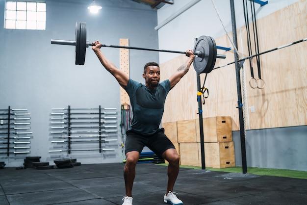 Crossfit спортсмен делает упражнения с штангой.
