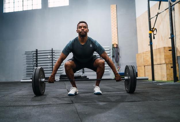 Спортсмен по кроссфиту делает упражнения со штангой.