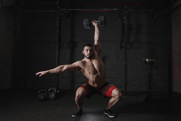 Кроссфит-спортсмен делает приседания с гантелями над головой в тренажерном зале