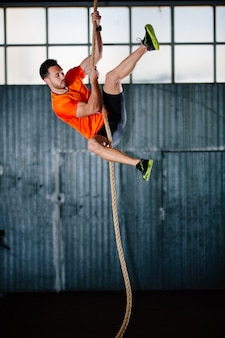 Crossfit athlete man climbing a rope in gym