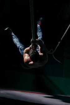 Concetto di crossfit con l'addestramento dell'uomo sulla corda