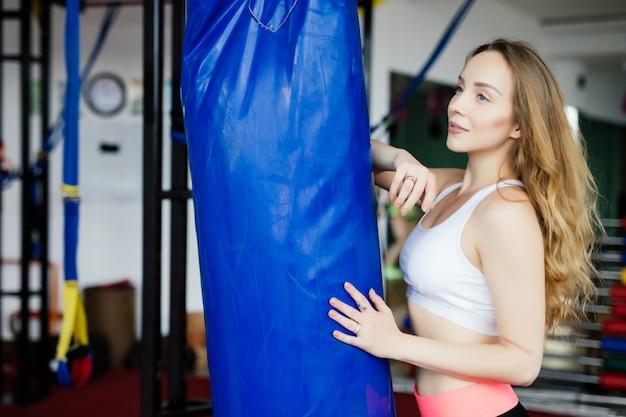 Crossfit fitness donna boxe con sacco da boxe blu in palestra