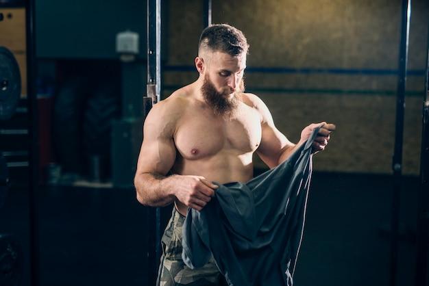 Crossfitジムでtシャツを保持している筋肉の魅力的な上半身裸の白人のひげを生やした男。