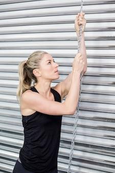 Подходящая женщина, держащая цепь в тренажерном зале crossfit