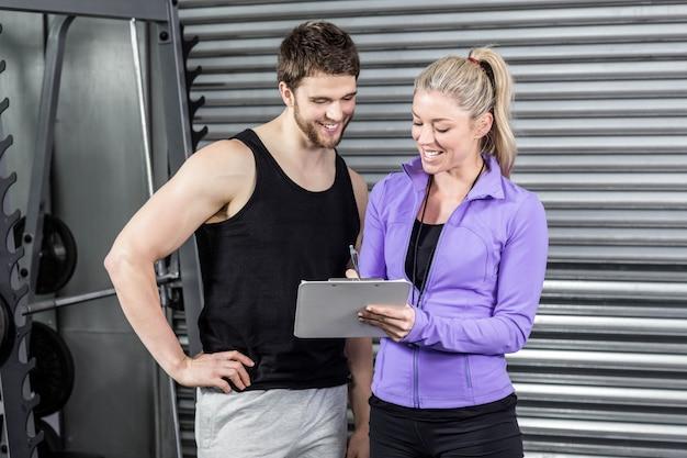 Женский тренер разговаривает с клиентом в тренажерном зале crossfit