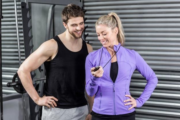 Женский тренер, показывая таймер в тренажерном зале crossfit