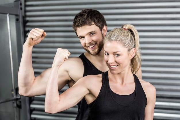 Crossfitジムで筋肉の腕を示すフィットカップル