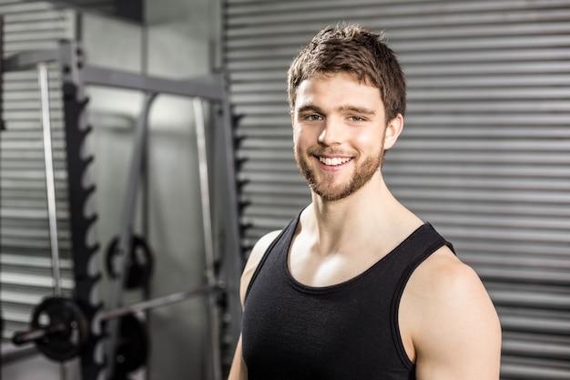 Улыбающийся здоровый мужчина позирует в тренажерном зале crossfit