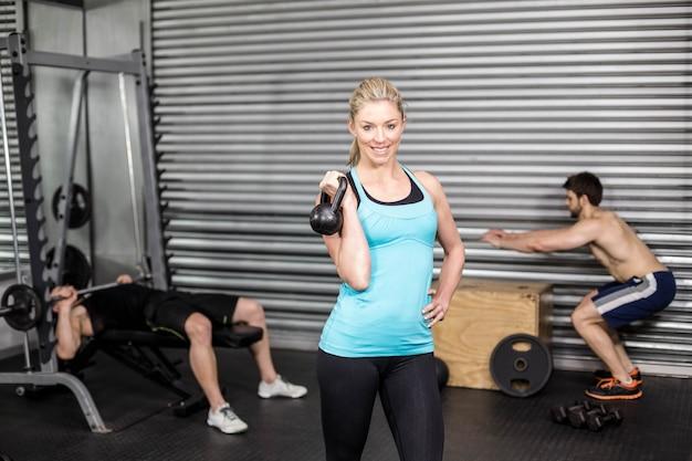 Женщина позирует с гантелями в тренажерном зале crossfit