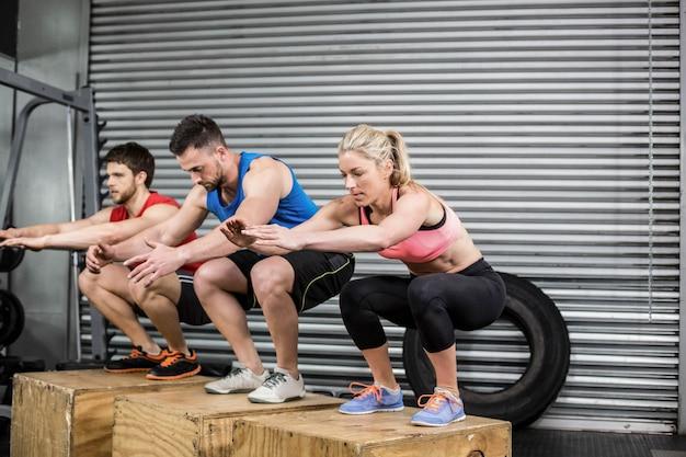 Подходящие люди делают упражнения с коробкой в тренажерном зале crossfit