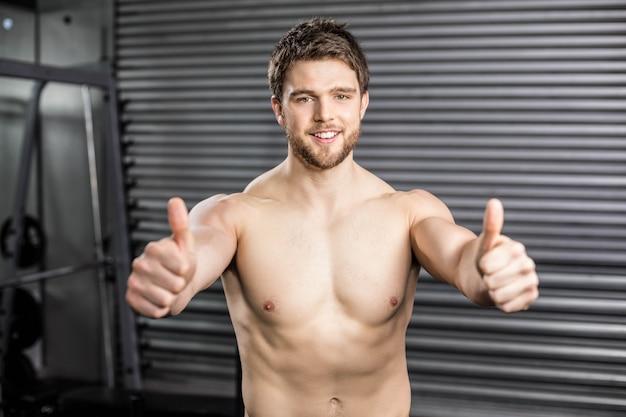 Подходящий без рубашки мужчина с большими пальцами в тренажерном зале crossfit