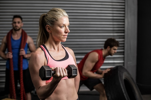 Портрет гантели подходящей женщины поднимаясь на спортзале crossfit