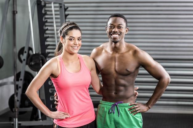 Улыбающаяся здоровая пара в тренажерном зале crossfit