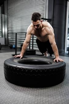 Crossfitジムで重いタイヤを弾く上半身裸の男