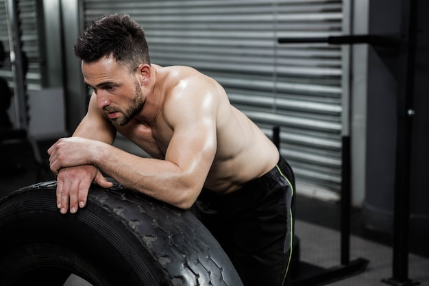 Crossfitジムで重いタイヤにもたれて疲れて上半身裸の男