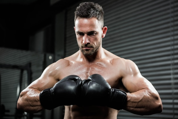 Crossfitジムでボクシンググローブを持つ怒っている上半身裸の男